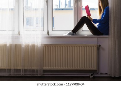 Leisure, literature and people concept. Young woman teen girl reading book at home while sitting on window sill. Blurred city view