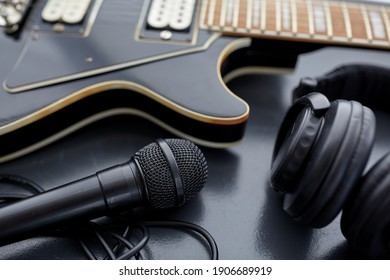 leisure, music and musical instruments concept - close up of bass guitar, microphone and headphones on black table