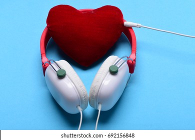 Leisure, music and Valentines day concept. Modern and stylish earphones isolated on turquoise background. Headphones in white and red color with soft heart. Headset for music and heart shaped player