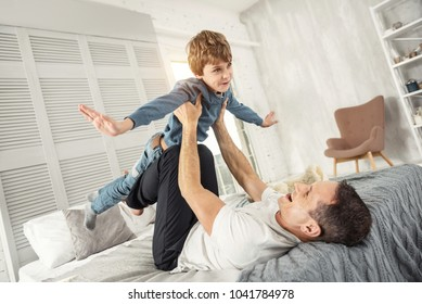 Leisure. Nice content fair-haired boy smiling and having fun with his daddy while lying on his back on the sofa