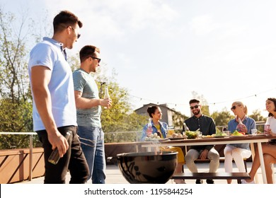 leisure and people concept - happy friends having barbecue party on rooftop