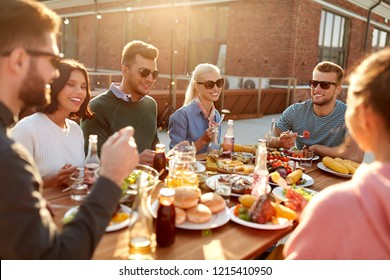 leisure and people concept - happy friends having dinner or barbecue party and eating on rooftop in summer