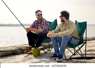 leisure and people concept - happy friends fishing and eating sandwiches on pier at sea