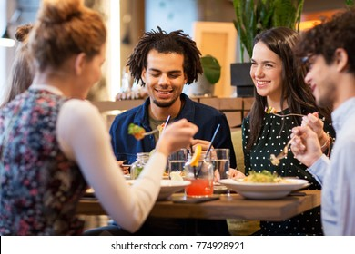 leisure and people concept - happy friends eating at restaurant
