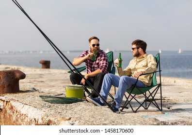 leisure and people concept - happy male friends fishing and drinking beer on pier