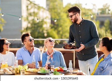 leisure and people concept - happy party host offering meat to his friends at bbq on rooftop in summer