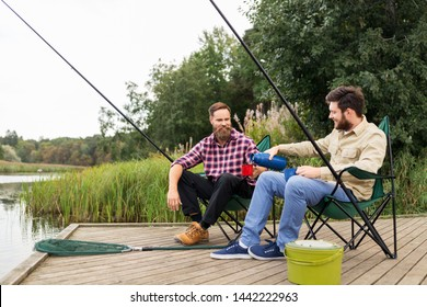 leisure and people concept - male friends fishing and drinking tea from thermos
