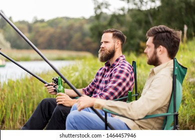 leisure and people concept - male friends fishing and drinking beer on lake