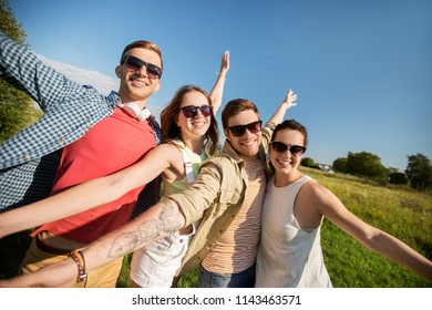 leisure, people and friendship concept - happy teenage friends having fun outdoors in summer