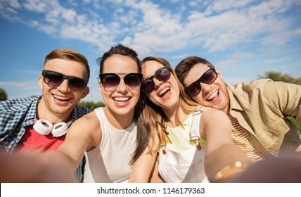 leisure, people and friendship concept - happy teenage friends taking selfie outdoors in summer