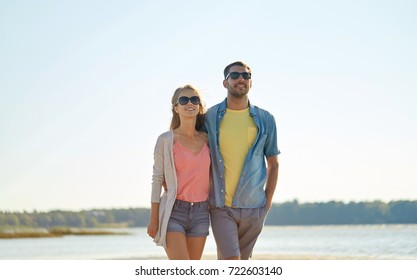 leisure, relationship and people concept - happy couple in sunglasses hugging on summer beach