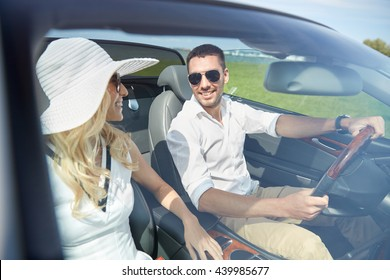 leisure, road trip, dating, couple and people concept - happy man and woman driving in cabriolet car outdoors