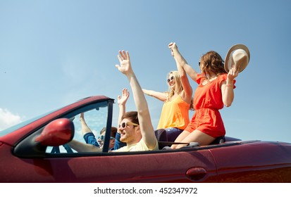 leisure, road trip, travel and people concept - happy friends driving in cabriolet car at country and waving hands