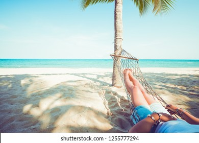 Leisure in summer - Beautiful Tanned legs of sexy women. relax and sunbathe on hammock at sandy tropical beach. vintage color styles