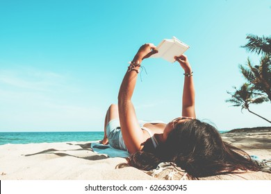 Leisure in summer - Young women lying on a tropical beach, relax with book. Blue sea in the background. Summer vacation concept. vintage color tone.
