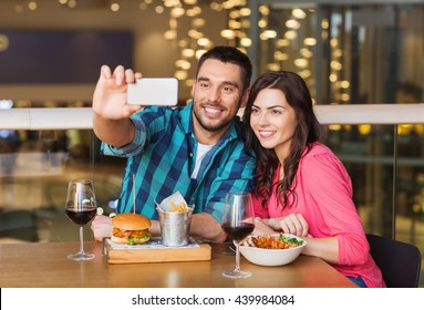 leisure, technology, date, people and holidays concept - happy couple having dinner and taking selfie by smartphone at restaurant
