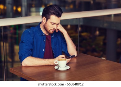 leisure, technology, lifestyle and people concept - man with smartphone and coffee at restaurant