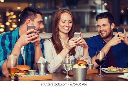 leisure, technology, lifestyle and people concept - happy friends with smartphones dining at restaurant