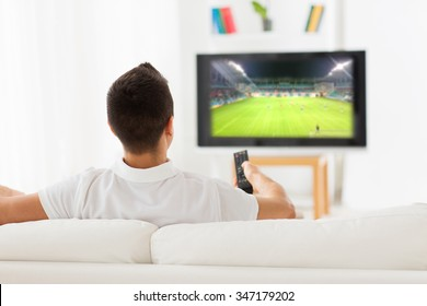 leisure, technology, media, sport and people concept - man watching football game on tv at home from back