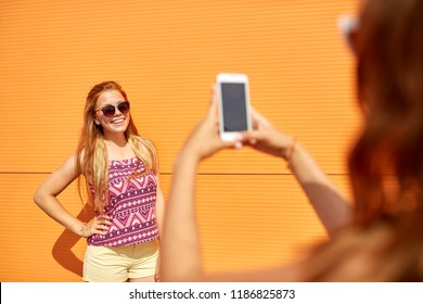 leisure, technology and people concept - teenage girl taking picture of her smiling friend by smartphone outdoors in summer
