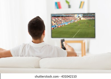leisure, technology, sport, entertainment and people concept - man with remote control watching football or soccer game on tv at home