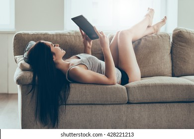 Leisure time at home. Beautiful young woman in panties and tank top holding digital tablet and looking at it with smile while lying on couch at home