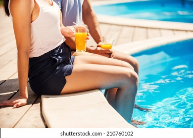 Leisure time poolside. Close-up of couple in casual wear sitting poolside together and drinking cocktails