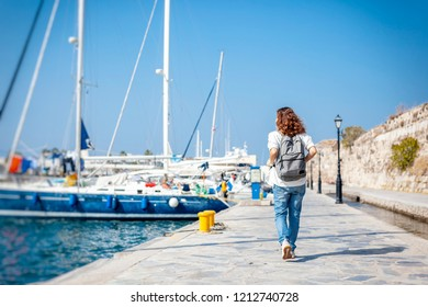 Leisure woman walking on holiday in yacht and sailboats marina resort town. Island Kos Greece, in Mediterranean Europe.