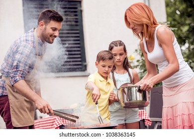 Leisure,food,people and holidays concept-man cooking meat on barbecue grill for his family at summer outdoor party.