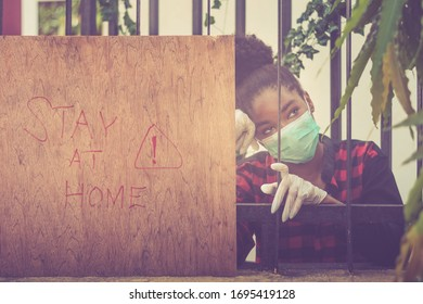 Lekki, Lagos / Nigeria - April 4 2020: Young girl wearing face mask to protect herself during the pandemic.  Warning sign can be seen