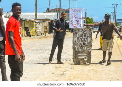 Lekki, Lagos / Nigeria - April 7th 2020: Street boys set up blockades to beg for money due to hunger caused by lack of jobs during the lockdown enforced in Nigeria, to prevent the coronavirus spread
