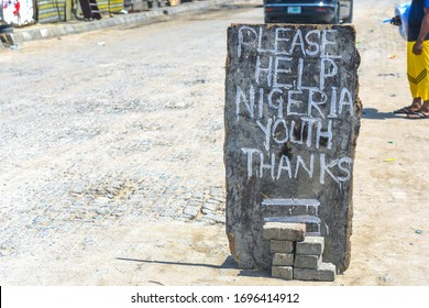 Lekki, Lagos / Nigeria - April 7th 2020: Hungry youths leave a sign begging for alms, as things get tougher in Nigeria due to the compulsory lockdown to prevent the spread of coronavirus