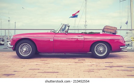 LELYSTAD, THE NETHERLANDS - JUNE 15, 2014: 1967 Red MG B on display during the annual National Oldtimer day. Filtered toned photograph in a retro nostalgic style.