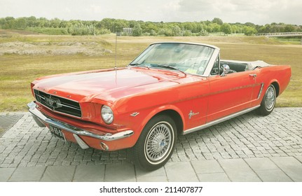 LELYSTAD, THE NETHERLANDS - JUNE 17 2012: 1965 Ford Mustang Convertible on display during annual National Oldtimer day. Textured photograph in a retro-like look.
