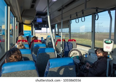 Lelystad, The Netherlands - March 14, 2018: Passengers in a bus travelling from Lelystad to Emmeloord. A woman is sitting beside her baby in a pram