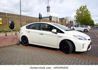 Lelystad, the Netherlands - September 1, 2019: White Toyota Prius being charged on a public parking lot. Nobody in the vehicle.