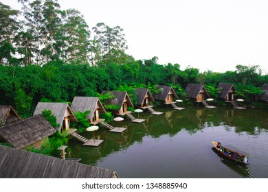 Lembang.Bandung/Indonesia - August 11th 2018: A lake surrounded by wooden houses with boats in Bamboo Village (Dusun Bambu)