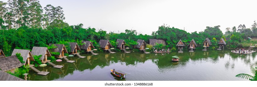 Lembang,Bandung/Indonesia - August 11th 2018: Panorama of a lake surrounded by wooden houses with boats in Bamboo Village (Dusun Bambu)
