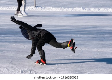 LEMMER, THE NETHERLANDS - FEBRUARY 13 2021: Boy in black winter clothes and colorful ice skates slips, lost his balance and falls on the ice, arms outstretched to catch the fall