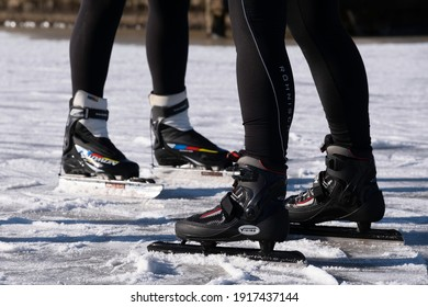 LEMMER, THE NETHERLANDS - FEBRUARY 14 2021: Low position of the feet of two skaters with branded shoes on skates with extra long iron  on the ice. Focus on the shoes of the man in front