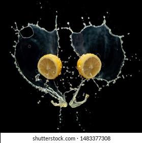 Lemom slice with juice splash isolated on black background