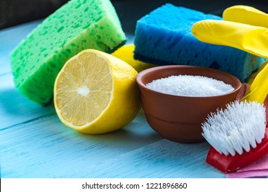 Lemon acid in a small plate, a juicy lemon, sponge for washing dishes, brushes and yellow rubber gloves for cleaning the house on wooden background. Natural cleaning products