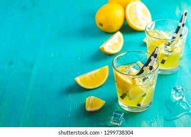 Lemon alcohol drink cocktail with ice, lemon and rosemary herb on a blue turquoise wooden table background surface. Traditional italian homemade lemon alcohol drink liqueur limoncello.