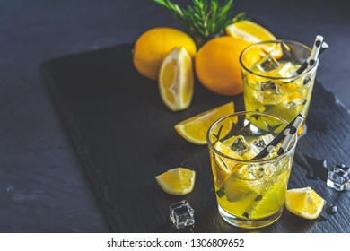 Lemon alcohol drink cocktail with ice, lemon and rosemary herb on black stone concrete surface. Traditional italian homemade lemon alcohol drink liqueur limoncello.