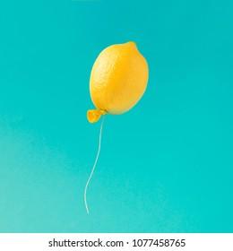 Lemon balloon on bright blue background. Minimal summer fun concept.