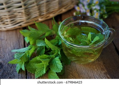 Lemon balm herbs tea with fresh leaves on wooden background