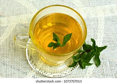 Lemon balm tea in a glass cup, top view.
