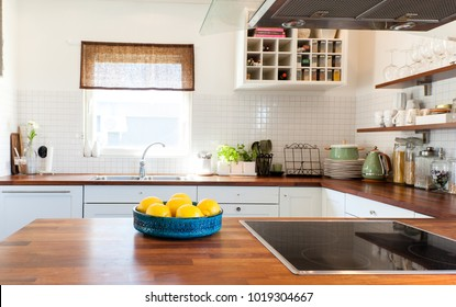 lemon in a bowl on the wooden counter top with kitchen in the background