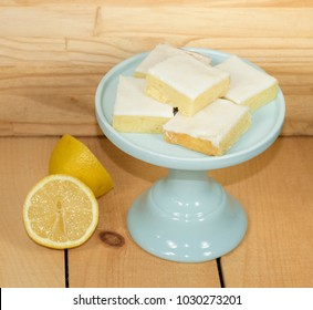Lemon brownies on a jade green cake plate and two lemon halves against a wood background