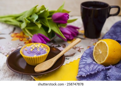 lemon cake with cream and tulips on a table, selective focus